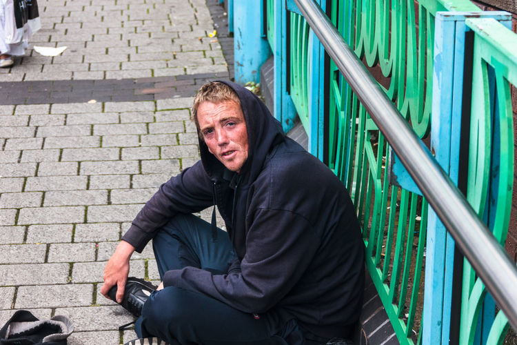 Young man sitting cross legged on the street begging wearing a blue hoody, and jeans. Adult Begging City City Centre Cobbled Streets Cross Legged Day Empty Streets Homeless Hoody Mid Adult No Filters Or Effects One Man Only One Mid Adult Man Only One Person Outdoors Portrait Railings Sitting Sitting Sitting Alone Social Issues Street Portrait Unprocessed Young Adult