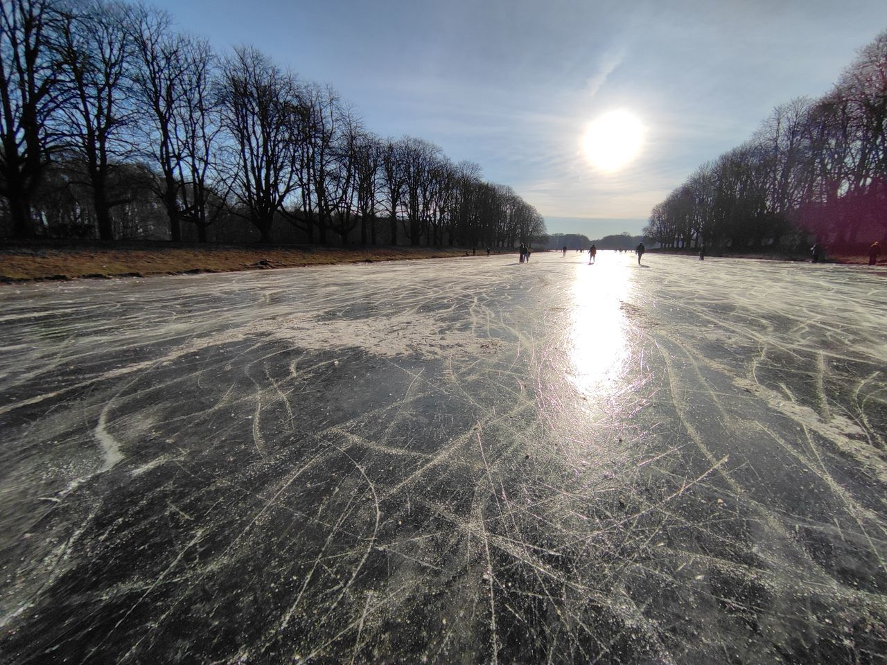 SCENIC VIEW OF FROZEN LAKE AGAINST SKY AT SUNSET