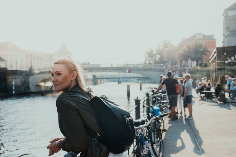 Woman on bicycle in city against sky