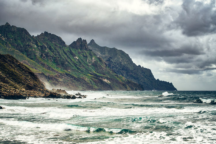 Coastline with foamy waves against rugged green mountain ridge under a stormy sky