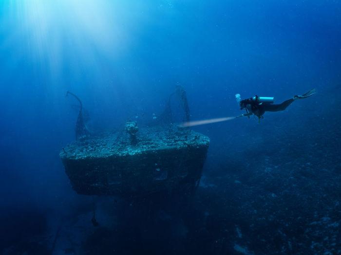 Person swimming in sea by shipwreck