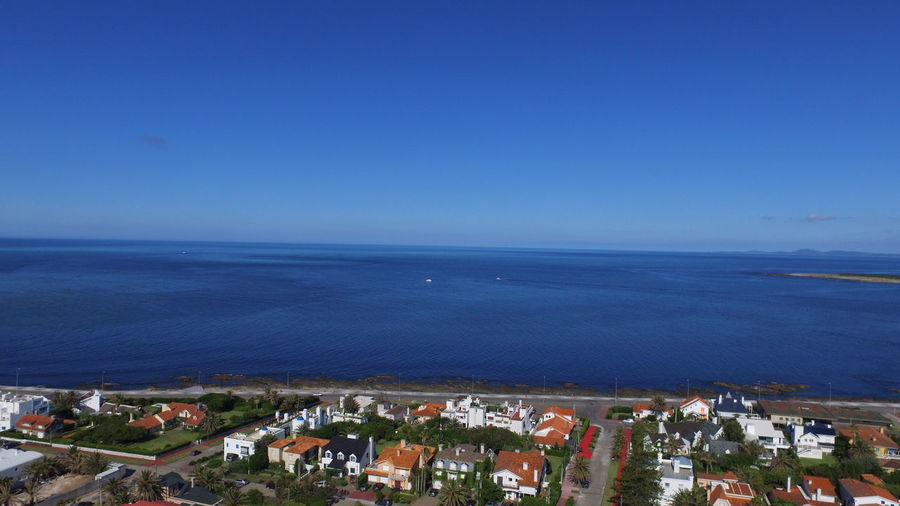 High angle view of sea and buildings against clear blue sky