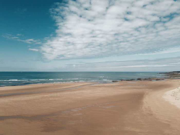 Scenic drone view of beach and ocean against sky