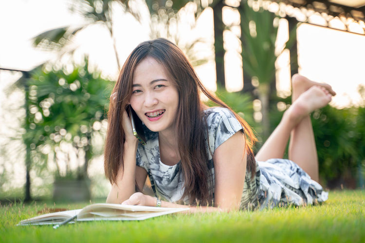 Young Adult Plant Lying Down Leisure Activity Publication One Person Young Women Grass Book Casual Clothing Portrait Lying On Front Real People Smiling Tree Lifestyles Nature Happiness Beautiful Woman Hair Hairstyle Outdoors