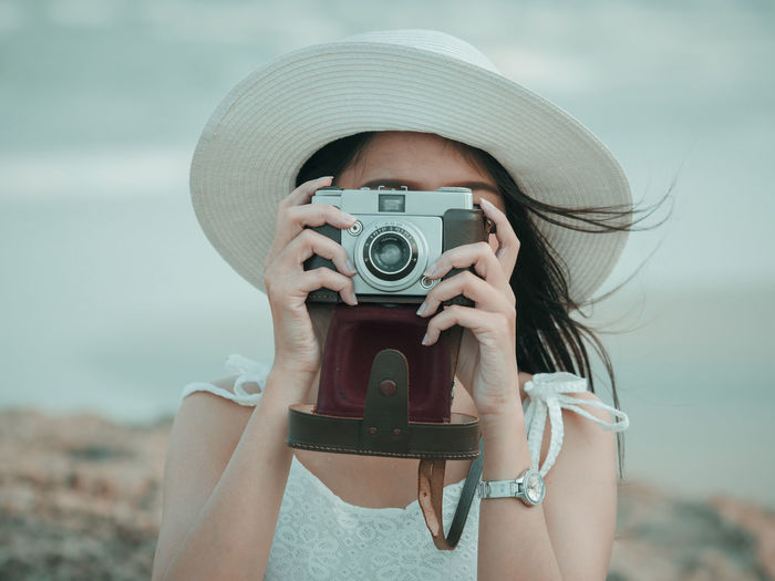 Camera Camera - Photographic Equipment Close-up Day Digital Single-lens Reflex Camera Focus On Foreground Front View Holding Human Hand Leisure Activity Movie Camera Nature One Person Outdoors Photographer Photographing Photography Themes Real People Sky Sun Hat Technology Water Young Adult Young Women