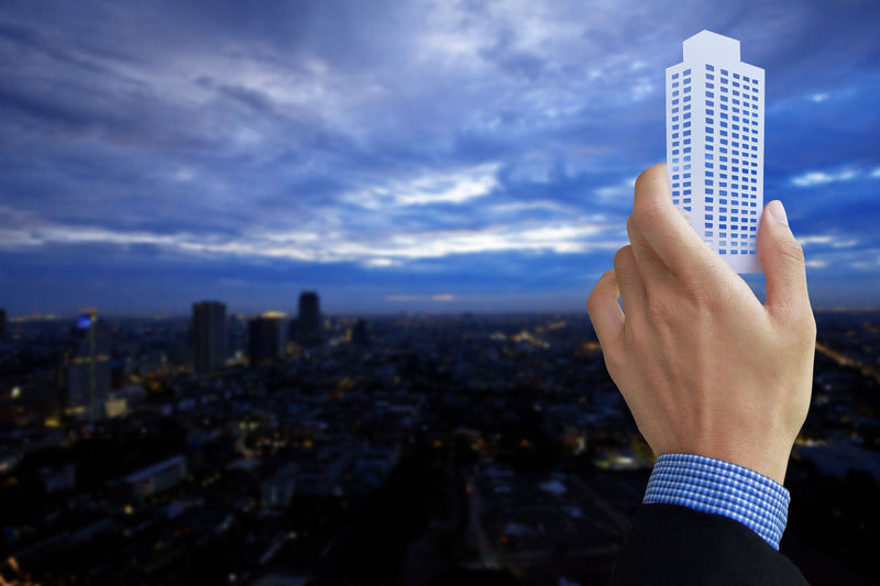 Cropped hand of businessman holding model over cityscape against cloudy sky at dusk