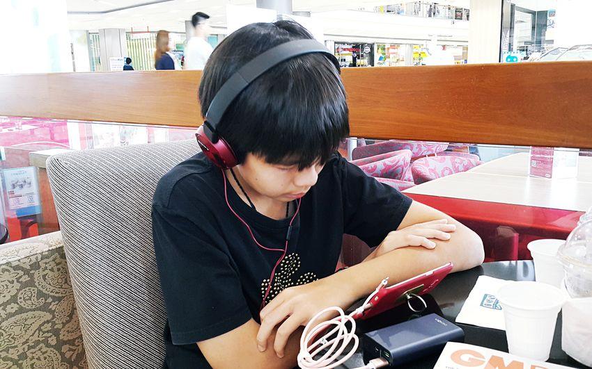 Full length of teenage girl sitting on table at restaurant