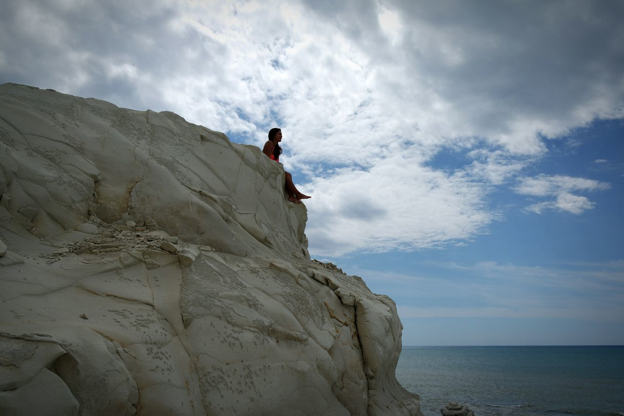 sky, cloud - sky, rock - object, nature, horizon over water, leisure activity, sea, full length, day, beauty in nature, one person, outdoors, low angle view, adventure, scenics, real people, climbing, rock climbing, young adult, cliff, lifestyles, men, water, people