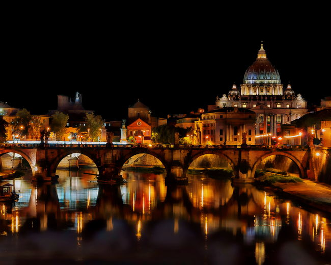 Ponte sant angelo over tiber river by st peter basilica at night