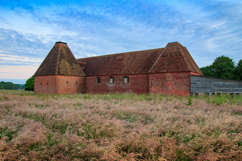 Oast House, Garden Of England, Kent, England. Architecture Sky Built Structure Nature No People Plant Hops Beer Brewing Iconic Buildings Vivid International Getty Images EyeEm Gallery Travel Destinations Tourism Sunrise Countryside Rural Scene History Building Exterior Building Field Cloud - Sky Land Grass House Old Day Landscape Abandoned Environment Wood - Material