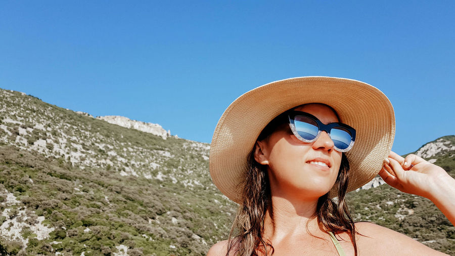 Portrait of young woman in summer. reflection of sea in sunglasses.