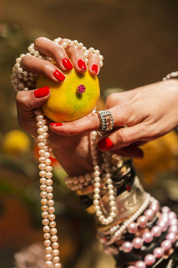 Gestures of a woman with jewelry, pearls, fruits and flowers. Abundance Wealth Celebration Art And Craft Mood Jewelry Gold Pearls Gesture Luxury Human Hand Hand Human Body Part One Person Holding Focus On Foreground Close-up Bracelet Adult Nail Polish Fruit Nail Women Body Part Human Finger Finger Food Red Beautiful Woman