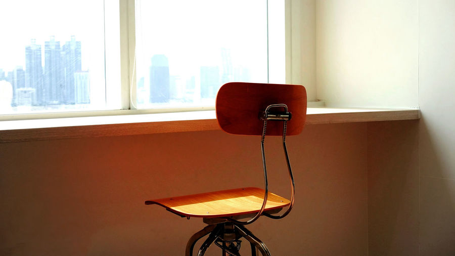 Empty chair by table against wall at home