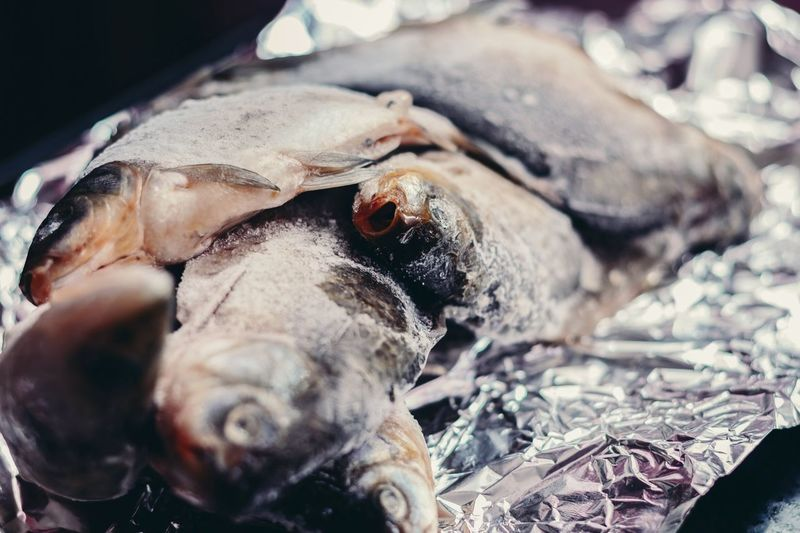 Close-up of frozen fish on foil for sale at market stall