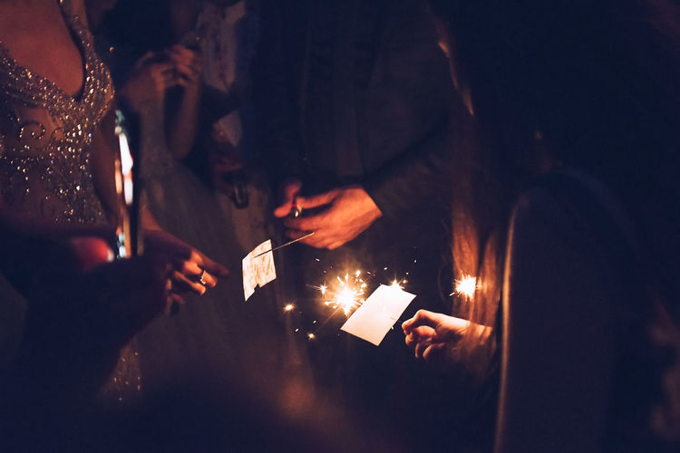 Midsection of people holding illuminated sparklers at night