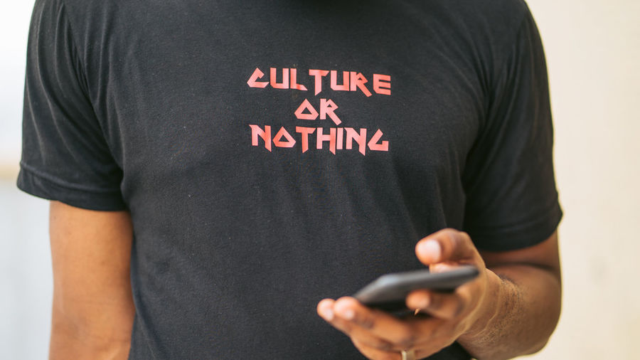 Culture or Nothing One Person Communication Midsection Men Technology Western Script Text Wireless Technology Casual Clothing Adult Indoors  Standing T-shirt Front View Telephone Mobile Phone Holding Connection Message