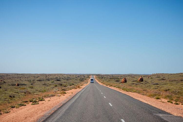 Road passing through desert against clear blue sky