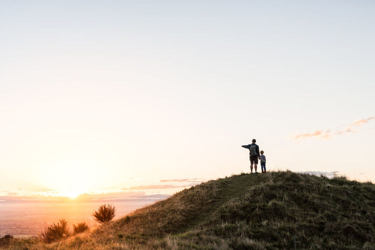 Silhouette man standing on hill against sky during sunset