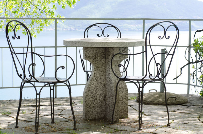 Patio with Chairs and a Table Chair High Up Patio Sunny Architecture Beauty In Nature Built Structure Day Furniture Iron - Metal Land Metal Nature No People Outdoors Plant Protection Railing Security Sunlight Table Tranquility Tree Water Wrought Iron