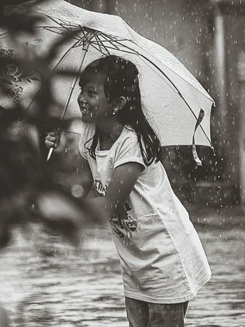 Looking for what is sought One Person Standing Real People Smile Outdoors Rainy Days Rain Raindrops Smiling Girl Blackandwhite Black & White Blackandwhite Photography
