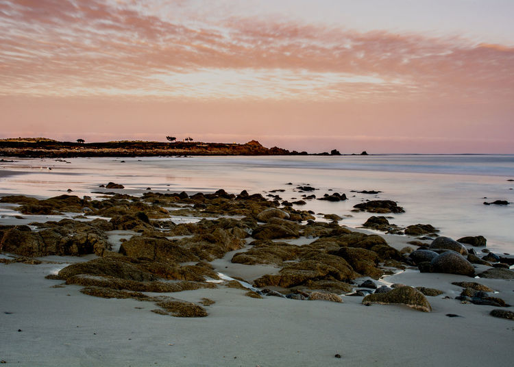 Long exposure landscape of the ocean nearPebble beach in the Pacific Grove, California, USA, on the 17-mile drive route in the winter of 2018, in the sunrise, featuring the rocks in the foreground and large copy space in the sky Long Exposure Sunrise Ocean Sea Coast Rocks Rocky Foreground Coastline Pebble Beach Monterey Peninsula County California USA 17-mile Seventeen Mile Drive Route Rugged Pacific Grove Terrain Cloudless Blue Colorful Pink Sky Water Tourist Attraction Landmark Travel Iconic Copy Space Sunny Day Panoramic Panorama Landscape West No People Sunset Beauty In Nature Tranquil Scene Tranquility Horizon Over Water Pacific Grove, Ca
