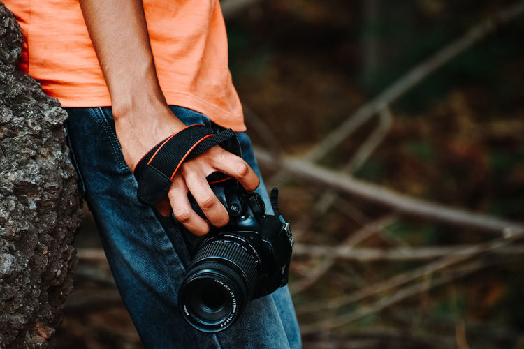 Midsection of man photographing with camera while standing by rock