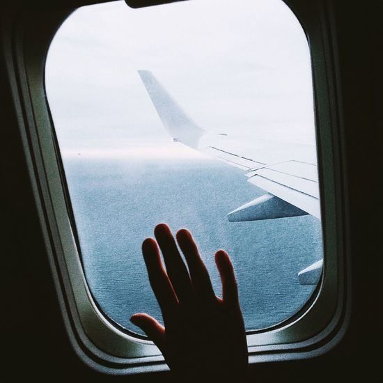 Cropped hand touching window in airplane