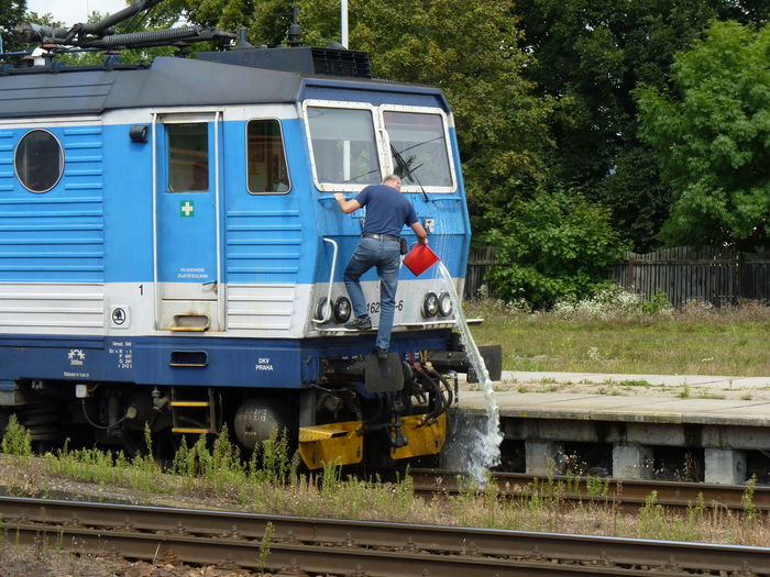 Man cleans windows Bucket Engine-driver Jeans Locomotive Locomotive Windows Man Public Transportation Running Water Water Waterfall Window Cleaning