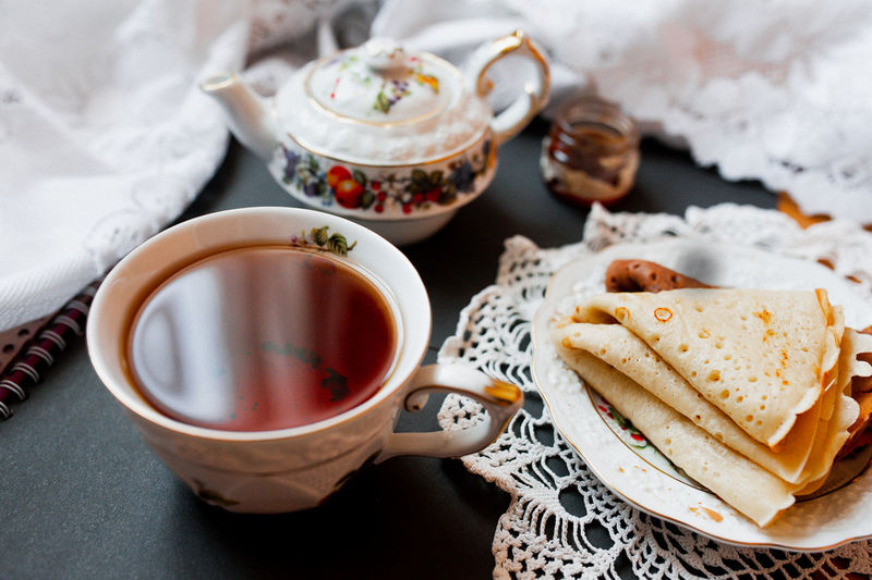 Beautiful version of breakfast with white porcelain cup and pancakes. maslenitsa