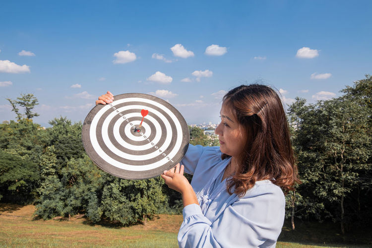 Young woman holding dart board against sky