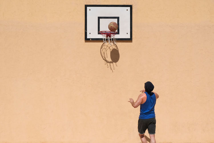 Basketball - Sport Lifestyles One Person Men Basketball Hoop Leisure Activity Real People Rear View Sport Team Sport Wall - Building Feature Ball Motion Basketball Player Competition Court Casual Clothing Basketball - Ball Vitality Copy Space Yellow Wall Fitness