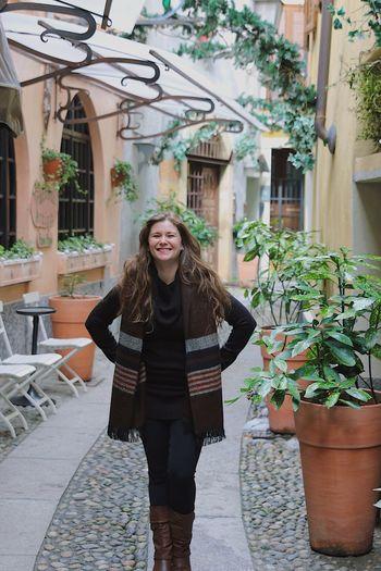 Portrait of smiling woman walking on footpath amidst buildings