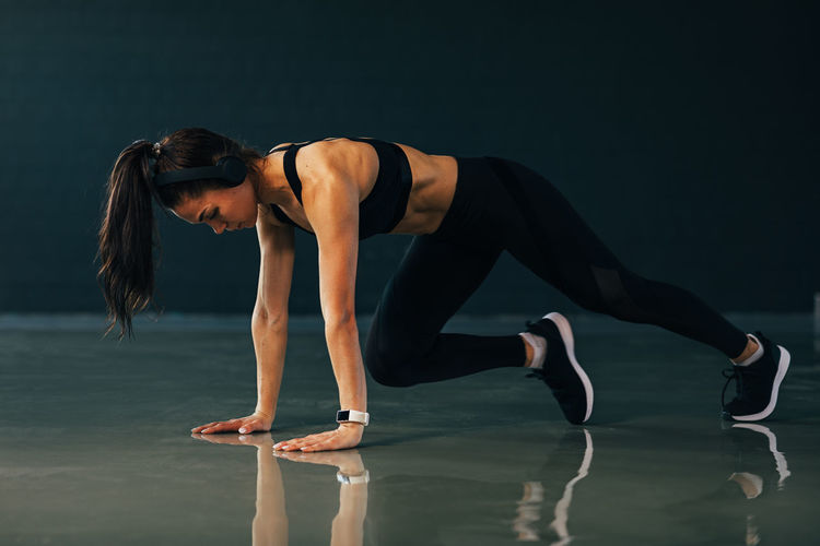 Side view of young woman exercising on floor at gym
