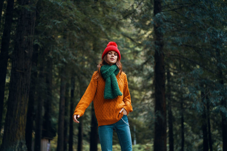 Portrait of young woman against trees in forest