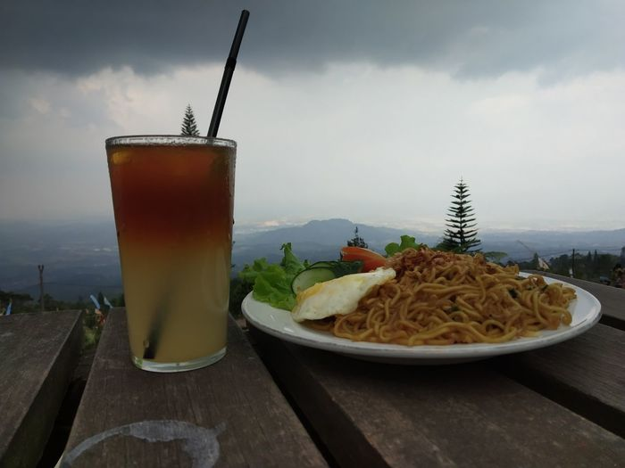 Food and drink on table against sky