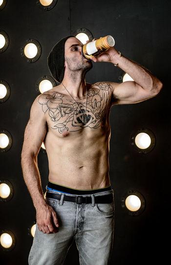 Shirtless man drinking coffee against illuminated lights