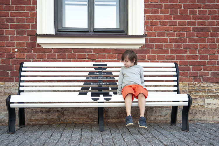Girl sitting on bench against brick wall