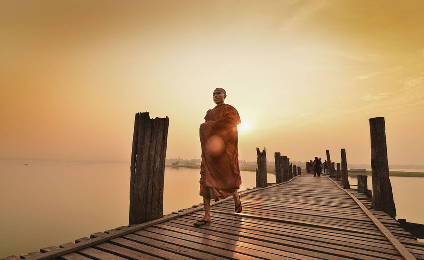 Full Length Of Monk Walking On Pier Over Sea Against Sky During Sunset