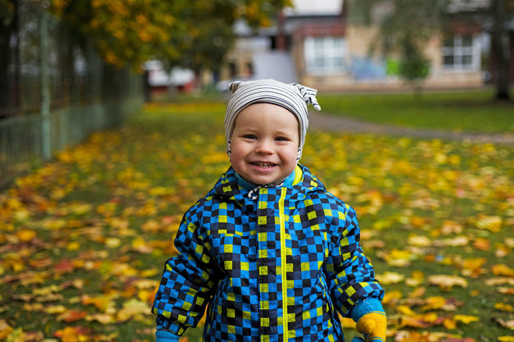 Portrait of happy boy standing against autumn leaves
