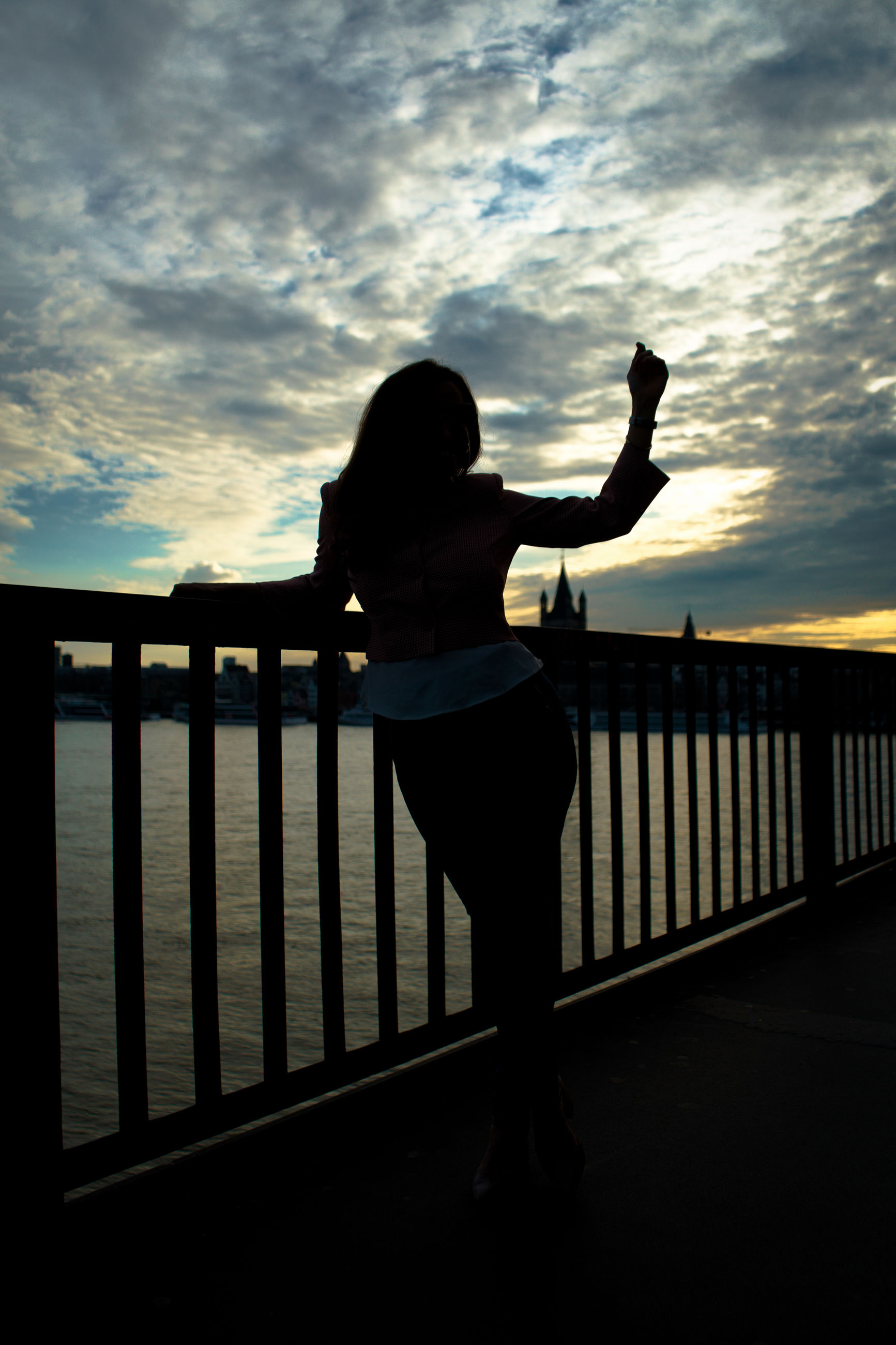sky, railing, cloud - sky, standing, sunset, silhouette, real people, one person, lifestyles, nature, architecture, leisure activity, water, sea, scenics - nature, full length, built structure, beauty in nature, human arm, outdoors, arms raised, leg