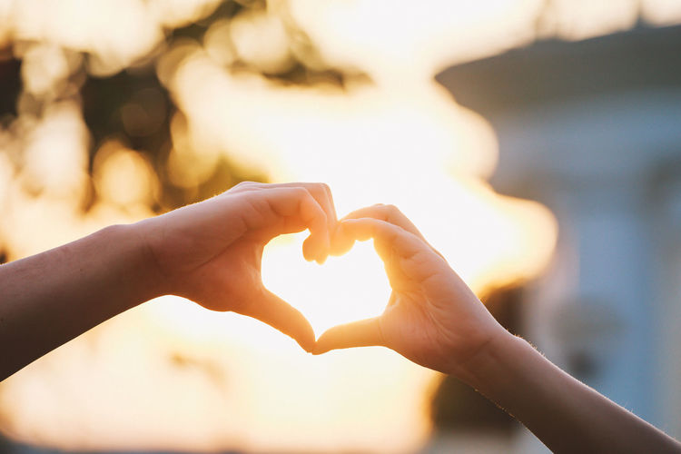 Heart shape made with hands of couple sunset background. Love symbol concept. Close-up Day Focus On Foreground Forming Heart Shape Holding Human Body Part Human Hand Love Outdoors People Real People Shape Sky Sunset Togetherness Two People Women