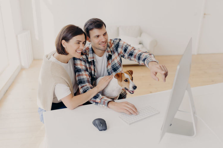 High angle view of smiling couple with dog using computer on table at home