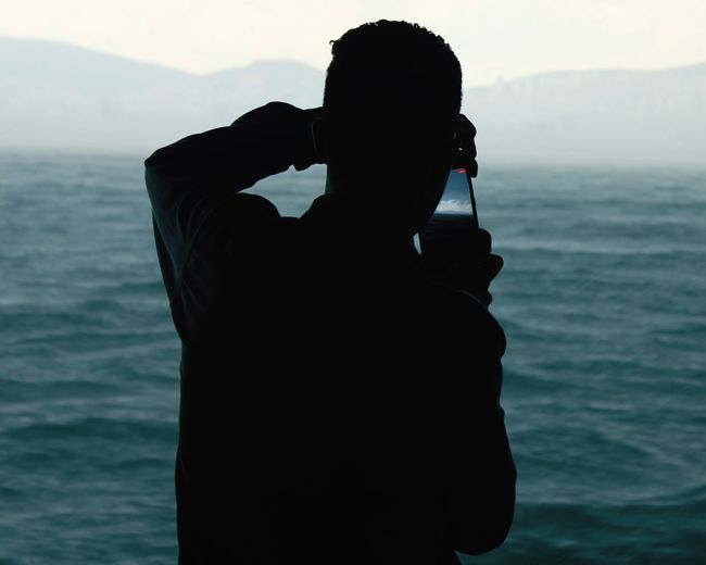 Rear view of silhouette man photographing sea