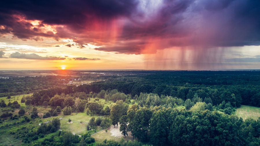 Rain pouring down from a dark heavy clouds on one side of the sky while setting sun is shining on the other side Flying High Beauty In Nature Cloud - Sky Day Dramatic Sky Field Forest Landscape Multi Colored Nature No People Outdoors Rural Scene Scenics Sky Storm Cloud Sunbeam Sunlight Sunset Tranquil Scene Tree