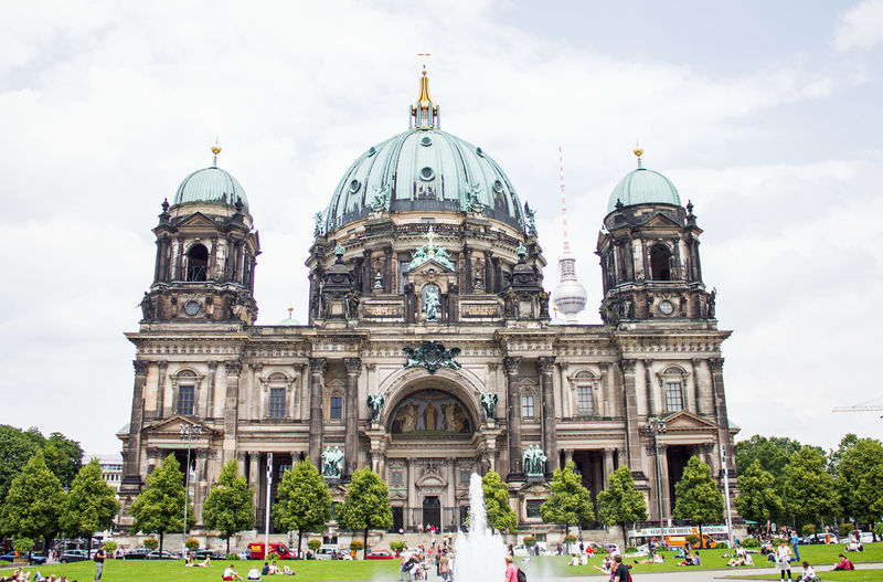 People in front of berlin cathedral against cloudy sky