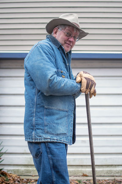 man in a denim jacket leans on a rake as he works outdoors on a fall day One Person Casual Clothing Standing Hat Real People Men Holding Senior Adult Adult Males  Clothing Architecture Senior Men Three Quarter Length Day Lifestyles Leisure Activity Focus On Foreground Jeans Cowboy Worker Outdoors Tools Of The Trade Raking Leaves Caucasian Ethnicity