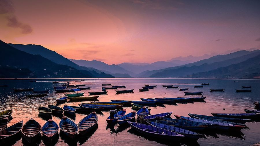Rowboats Moored In Lake Against Sky During Sunset