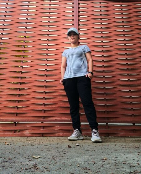 Full length portrait of a woman standing against steel wall