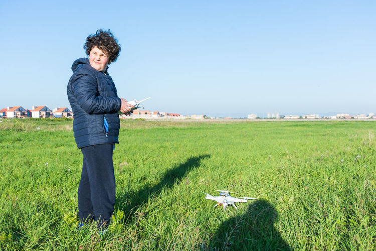 Drone  Agriculture Beautiful Woman Blue Clear Sky Curly Hair Day Field Full Length Grass Green Color Looking At Camera Nature One Person Only Women Outdoors Portrait Real People Standing Technology Wireless Technology Women Young Adult Young Women