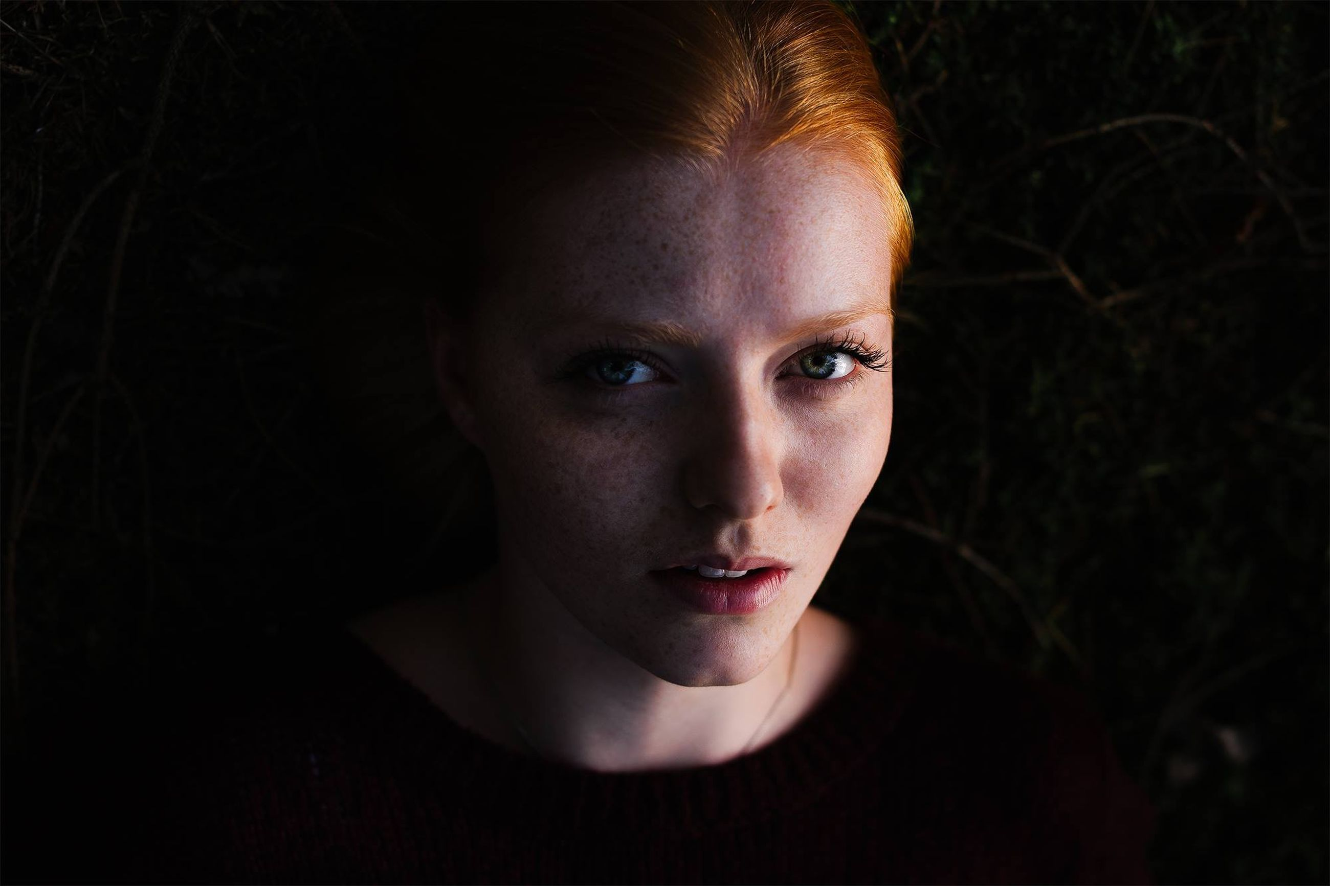 portrait, looking at camera, headshot, close-up, young adult, person, front view, human face, serious, studio shot, black background, indoors, lifestyles, contemplation, head and shoulders, staring, young women